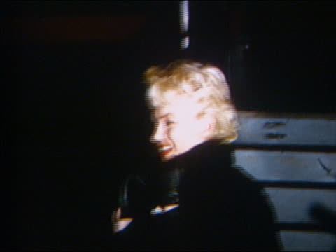 stockvideo's en b-roll-footage met 1950s close up marilyn monroe posing for cam after leaving airplane at night / flash bulbs going off - marilyn monroe