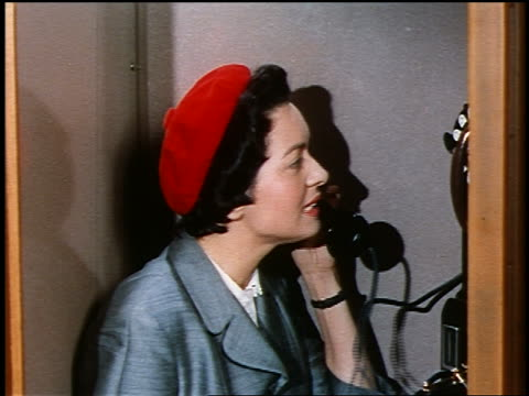 1950s close up profile woman in red beret talking on telephone in telephone booth - 電話ボックス点の映像素材/bロール