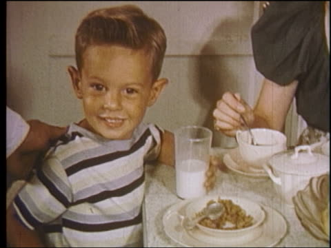 1950s close up small boy with milk mustache sitting at breakfast table + smiling up at man / educational - solo bambini maschi video stock e b–roll