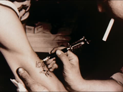 vídeos y material grabado en eventos de stock de 1950s close up tattoo artist with cigarette hanging out of his mouth as he works on customer's arm / coney island / brooklyn, new york / audio - fumar actividad