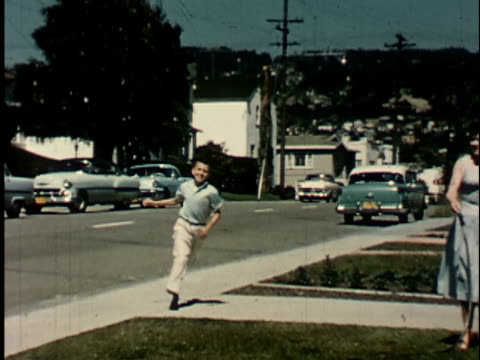 1950s ws, ms, composite, boy (14-15) running down sidewalk, showing peace of paper to parents in front of house, berkeley, california, usa - 14 15 jahre stock-videos und b-roll-filmmaterial