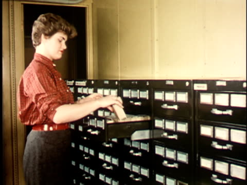 1950s MS, CU, COMPOSITE, Female student taking microfilm reel from file drawer at Berkeley University, 1950's, California, USA