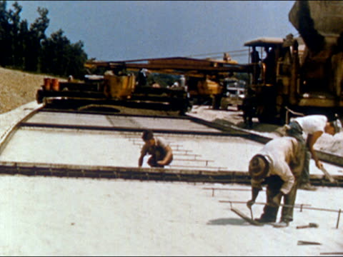 stockvideo's en b-roll-footage met 1950s construction crew laying down steel supports for highway / usa / audio - tweebaansweg