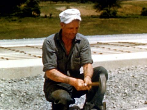 stockvideo's en b-roll-footage met 1950s construction worker hammering at highway construction site / usa / audio - stilstaande camera