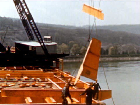 1950s construction workers assembling large pieces of steel being lowered by crane onto frame of bridge under construction over river / usa / audio - bridge built structure stock videos and b-roll footage