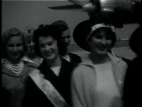 vidéos et rushes de 1950s ms contestants in a beauty pageant posing in a line at an airport / long beach, california, united states - 1955