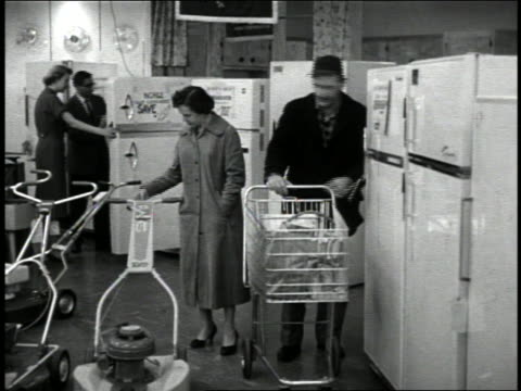 vidéos et rushes de b/w 1950s couple pushing shopping cart looking at price tags on refrigerators + lawn mowers - caddie