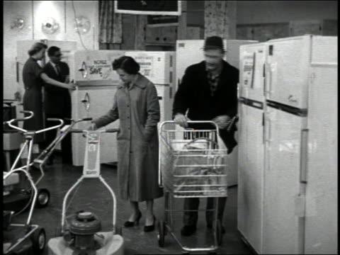 b/w 1950s couple pushing shopping cart looking at price tags on refrigerators + lawn mowers - frigorifero video stock e b–roll