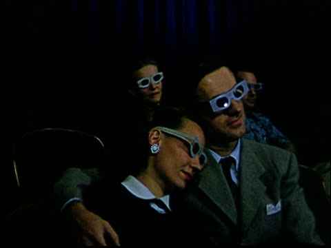 vídeos de stock, filmes e b-roll de 1950s ms couple sitting in movie theater wearing 3-d glasses/ man sitting down behind them and putting on glasses - óculos de terceira dimensão