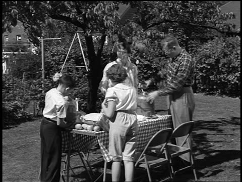 b/w 1950s couple + two children putting food on picnic table + sitting down to eat in yard - yorkville illinois stock videos & royalty-free footage