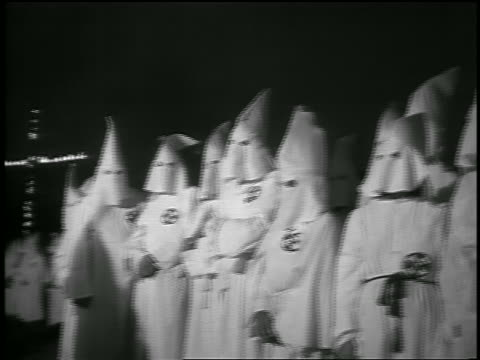 vídeos de stock, filmes e b-roll de b/w 1950s pan crowd of members of ku klux klan with burning cross in background at night / georgia - ku klux klan