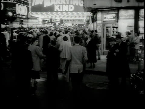 1950s ws crowd of people crossing street to a theater at night / new york city, new york, united states - documentary footage stock videos and b-roll footage