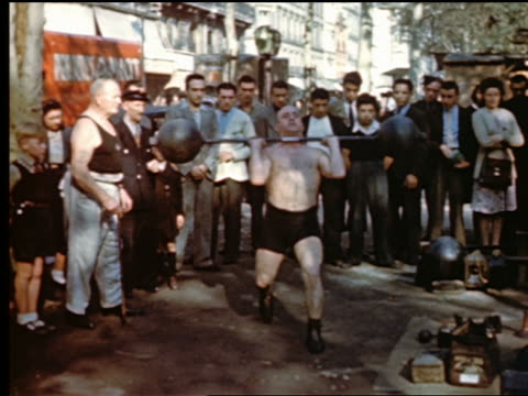 stockvideo's en b-roll-footage met 1950s crowd watching strongman / weight lifter lifting barbell over his head / paris, france - zwaar