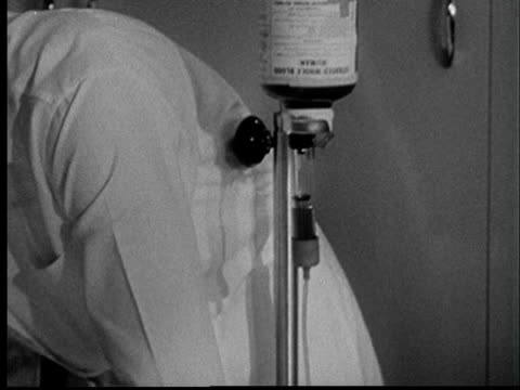 """1950s ms td doctor connecting blood tube to elderly woman lying in bed/ st. louis, missouri"" - flasche stock-videos und b-roll-filmmaterial"