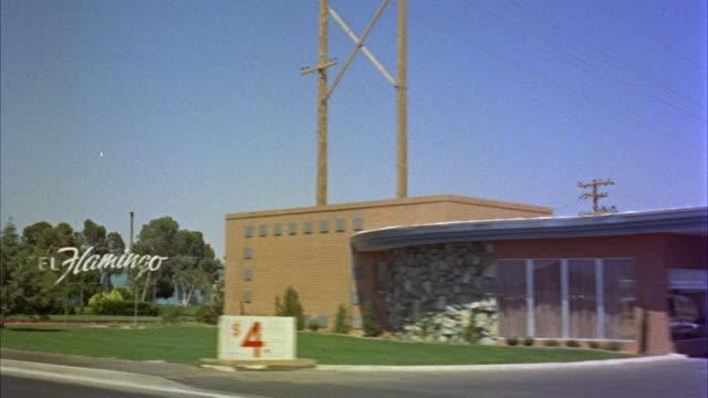 vídeos de stock e filmes b-roll de 1950s ws pov driving past desert villa motel and flamingo hotel / las vegas, nevada, usa - 1950 1959