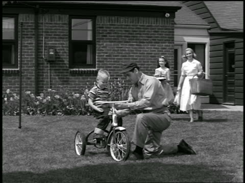 b/w 1950s father showing son features of tricycle on lawn / sister + mother in background with picnic basket - picnic basket stock videos & royalty-free footage
