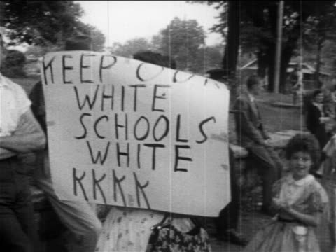 b/w 1950s pan female prosegregation protestor with sign keep our white schools white kkkk - rassismus stock-videos und b-roll-filmmaterial