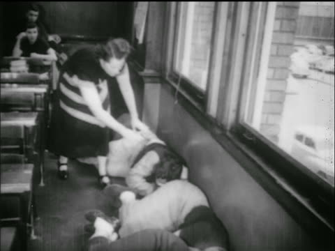 vídeos de stock e filmes b-roll de b/w 1950s female teacher adjusts students lying on floor of classroom / civil defense drill - simulacro de emergência