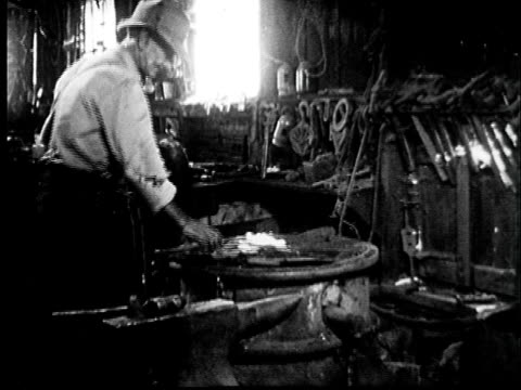 1950s film montage ms blacksmith forging hot metal wtih hammer/  cu hammering metal on anvil/ audio - metal industry stock videos and b-roll footage