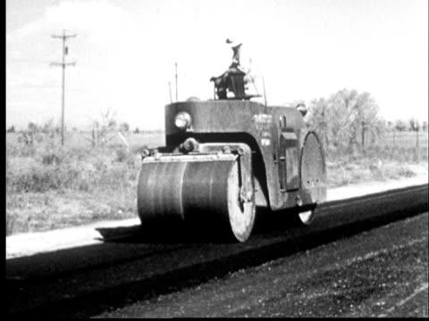 vídeos de stock e filmes b-roll de 1950s film montage ws man driving steamroller over freshly laid asphalt/ cu wheel of steamroller/ colorado - cilindro veículo terrestre comercial