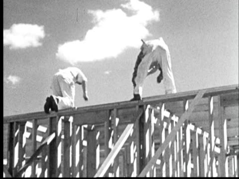 """1950s film montage  workers hammering on top of wooden house frame/ broomfield, colorado"" - bib overalls stock videos & royalty-free footage"