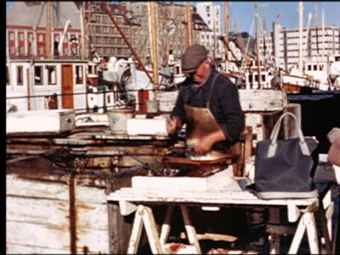 1950s fisherman cutting up fish on dock in marina / Norway