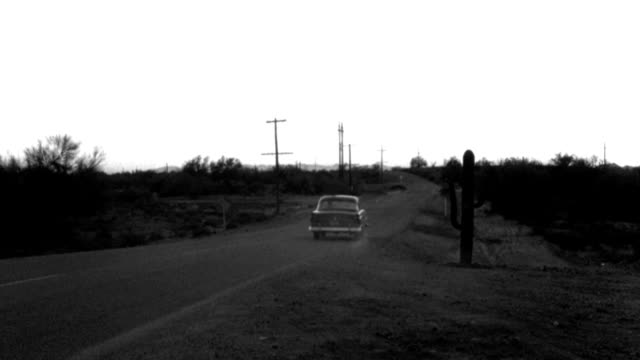 a 1950s ford turns onto a desert highway and drives off into the distance. - 1959 stock videos & royalty-free footage