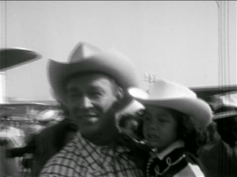 stockvideo's en b-roll-footage met b/w 1950s pan from roy rogers holding young girl to dale evans gesturing excitedly at airport - cowboyhoed