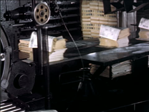 stockvideo's en b-roll-footage met 1950s pan from woman at assembly line to stack of newspapers on conveyor belt - drukpers