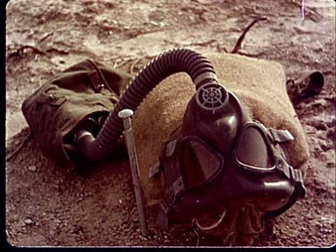 1950s CU Gas mask on stuffed burlap bag lying in desert at Camp Desert Rock at Nevada Test Site / Nye County Nevada USA