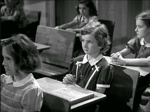 b/w 1950s girl wearing cross + sitting at desk raising hand in classroom - schoolgirl stock videos and b-roll footage