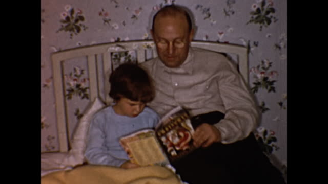 "1950s Grandfather reads to child in bed ""The Night Before Christmas"""