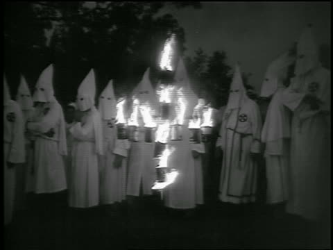 vídeos de stock, filmes e b-roll de b/w 1950s group of ku klux klan members walking past burning cross at night / georgia / documentary - ku klux klan