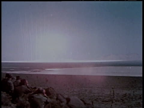 1950s ws group of men watching an atomic bomb going off in the distance / united states - nuclear bomb stock videos & royalty-free footage