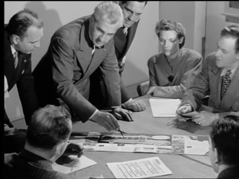 B/W 1950s group of men + woman looking at + talking about picture on table during meeting