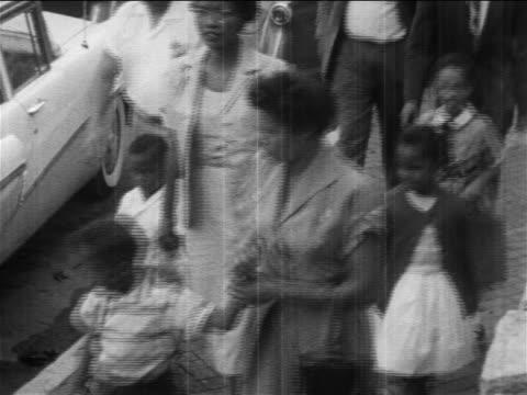 1950s high angle black parents walking their children to desegregated school / newsreel - dominering bildbanksvideor och videomaterial från bakom kulisserna