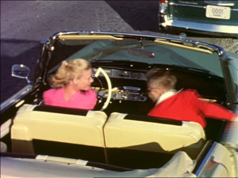 1950s high angle boy getting into convertible lincoln with woman / industrial - ford motor company stock videos and b-roll footage
