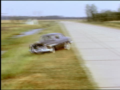 1950s high angle pan car driving off road into ditch full of water - wreck stock videos & royalty-free footage