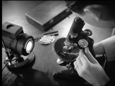 B/W 1950s high angle close up over-the-shoulder man looking through microscope at slide in laboratory