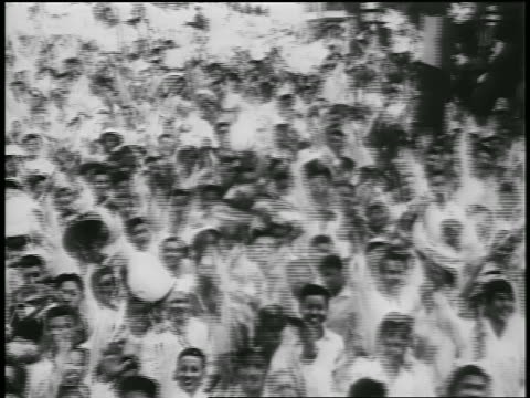 B/W 1950s high angle PAN crowd of excited North Vietnamese people cheering waving jumping up down