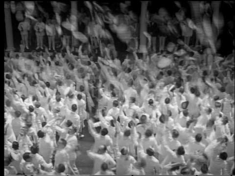 B/W 1950s high angle crowd of US Navy officers tossing caps into air at Annapolis graduation