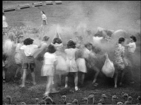 b/w 1950s high angle large group of women having large pillow fight in field with turkeys - kopfkissen stock-videos und b-roll-filmmaterial