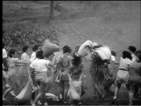 b/w 1950s high angle large group of women having pillow fight in field outdoors with turkeys in background - pillow fight stock videos & royalty-free footage