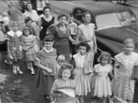1950s high angle pro-segregation women protestors walking with children on sidewalk / newsreel - dominering bildbanksvideor och videomaterial från bakom kulisserna