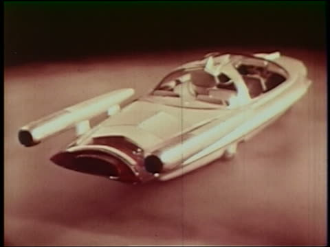 1950s high angle REAR VIEW futuristic sports car with bubble roof spinning on smoky platform
