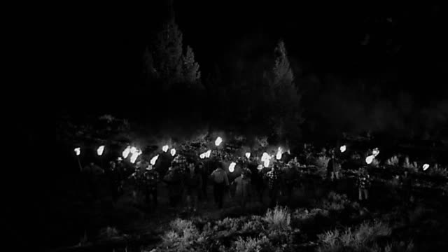 1950s high angle wide shot group of men in search party with torches walking through forest toward CAM at night