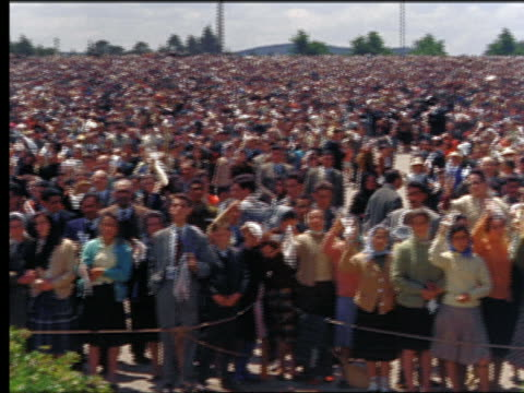 1950s high angle wide shot pan large crowd of people waving white handkerchiefs outdoors / portugal - protestor stock videos & royalty-free footage