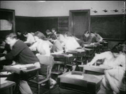 vidéos et rushes de b/w 1950s high school students in classroom jumping from seats drop to floor / civil defense drill - cinématographie