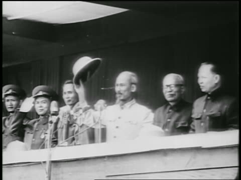 B/W 1950s Ho Chi Minh raising hat surrounded by others on balcony / North Vietnam / newsreel