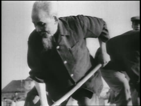 B/W 1950s Ho Chi Minh shoveling dirt outdoors / North Vietnam / newsreel